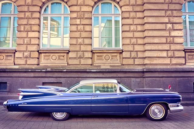 Amerykański krążownik szos - antyk Cadillac w niebieskim kolorze przed zabytkowym budynkiem