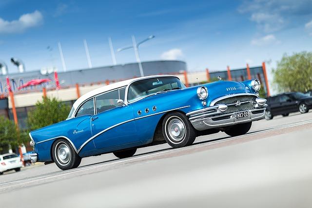 Niebieski oldtimer na parkingu przed centrum handlowym